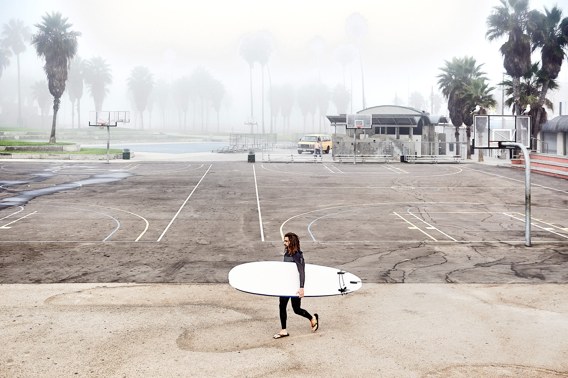 Venice Beach Dawn surfer walking across basket ball courts